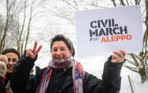 Signora con gesto di vittoria e cartello della marcia 12 -1-17