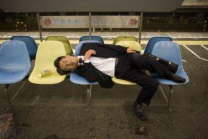 Giapponese che dorme su panchine- Overwork